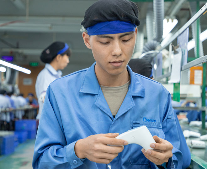 a male worker sitting at the assembly line is assembling an infrared thermometer