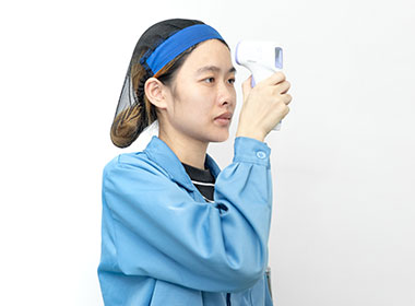 a female worker is testing an infrared thermometer's function