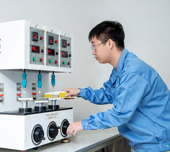 a male engineer conducting button life testing with a device