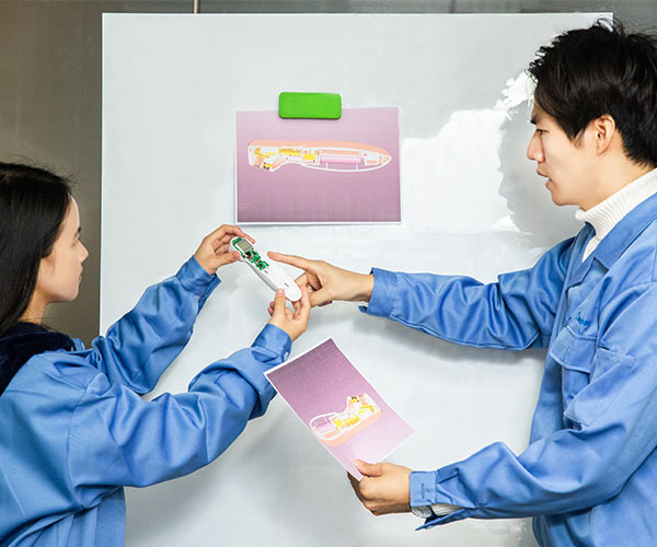 two engineers discussing an infrared thermometer's design